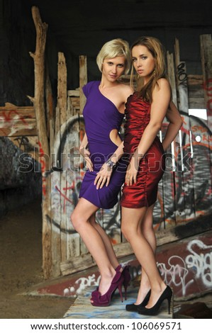 Two girls wearing colorful prom dresses on location