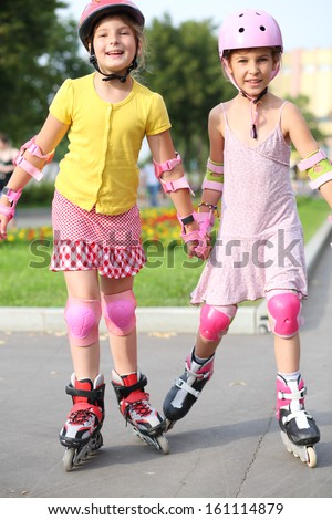 Two girls wearing helmets, elbow pads and knee pads ride on roller skates in the park - stock photo