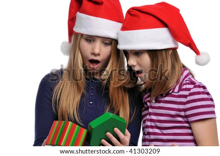 Two girls wearing Santa hats with christmas present isolated on a white background
