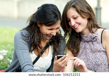 Two girls While They Speak with a cellular