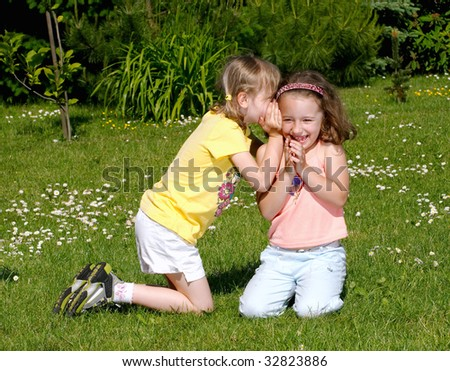 Two girls whispering secrets to each other - stock photo