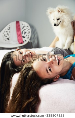 two girls with a Pomeranian lay on the bed and laughing close-up. vertical format - stock photo