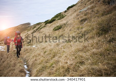 Two girls with backpacks walk along a trail in the mountains. - stock photo