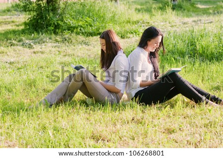 two girls with books outdoor - stock photo