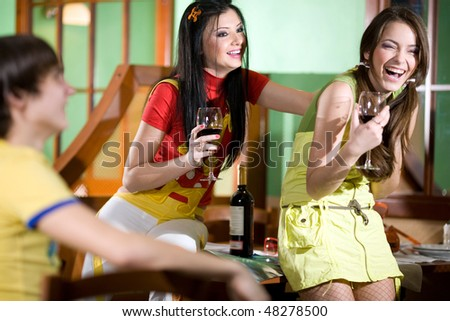 Two girls with boy are drinking wine