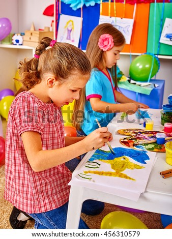 Two girls with brush painting on table in primary school. Painting lesson in class school. - stock photo