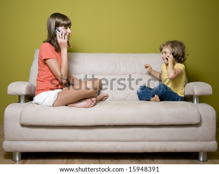 Two girls with cellular phones on sofa - stock photo