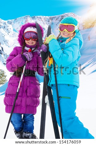Two girls with crosscountry ski standing together with mountains on background - stock photo
