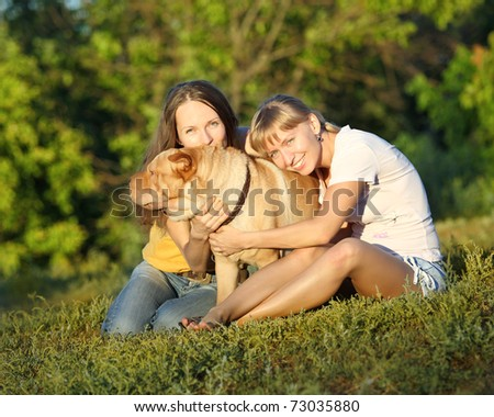 Two girls with dog in summer - stock photo