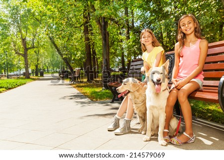 Two girls with dogs sitting in park on bench - stock photo