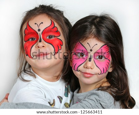 Two girls with face painting of a butterfly. - stock photo
