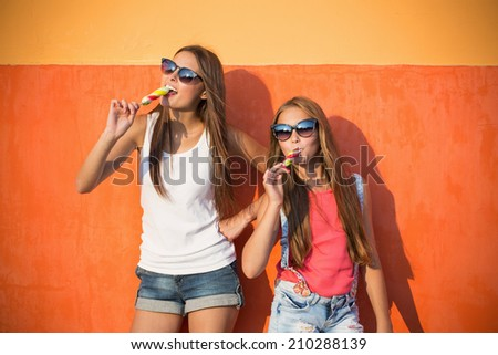 two girls with ice-cream on background wall - stock photo