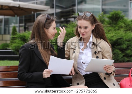 Two girls with papers and tablet computers talk on a park bench sunny day - stock photo