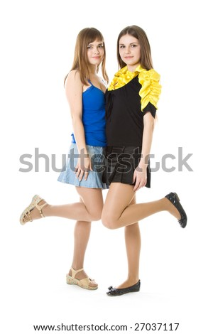 Two girls with raised leg isolated on white background
