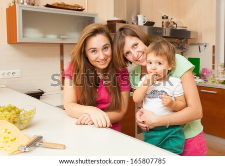 two girls with the baby in the kitchen - stock photo