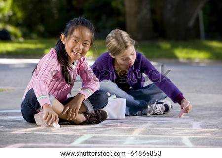 Two girls, 7 years, drawing pictures on driveway with chalk - stock photo