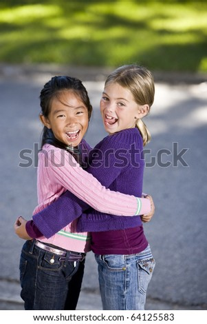 Two girls, 7 years, hugging and laughing - stock photo