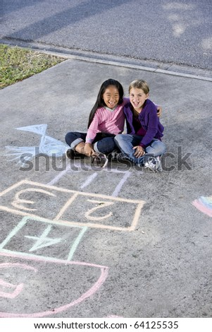 Two girls, 7 years, sitting in front of hopscotch board and other chalk drawings - stock photo