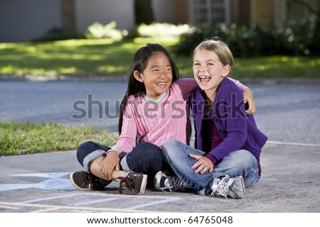 Two girls, 7 years, sitting together on driveway laughing - stock photo