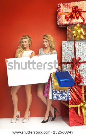 Two glamorous women holding a sale board - stock photo
