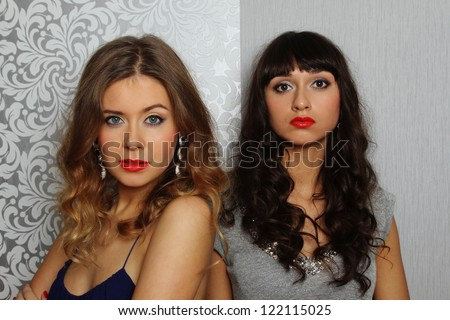 Two glamorous young women. Hairstyles, makeup, clothing