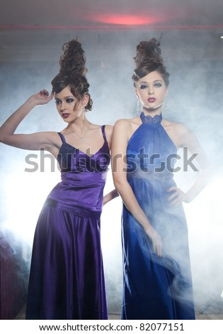 Two glamour girls the twins, one in a dark blue dress another in the violet pose in a smoke - stock photo