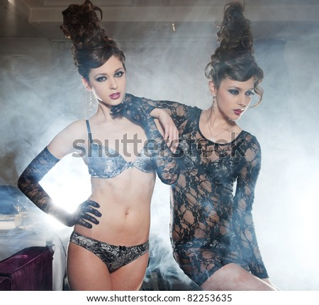 Two glamour girls twins, in underwear, pose in a smoke - stock photo