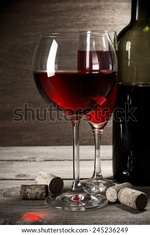 Two glass and bottle of red wine with corks on rustic wooden background.