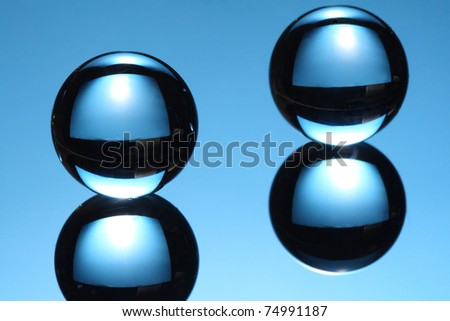 Two glass balls on a glass table - stock photo