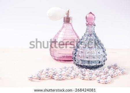 Two glass bottles of female perfume on a white background. Pink toning. - stock photo