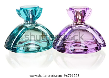 two glass bottles of perfume blue and lilac colors. Isolated on a white background with the reflection. - stock photo