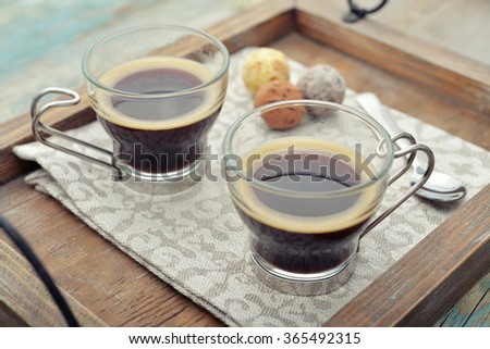 Two glass cups of coffee on wooden tray - stock photo