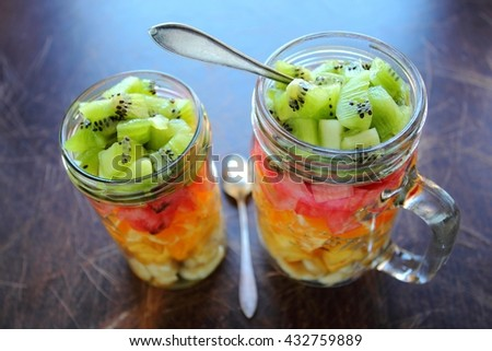 Two glass jars with sweet fruit salad - stock photo