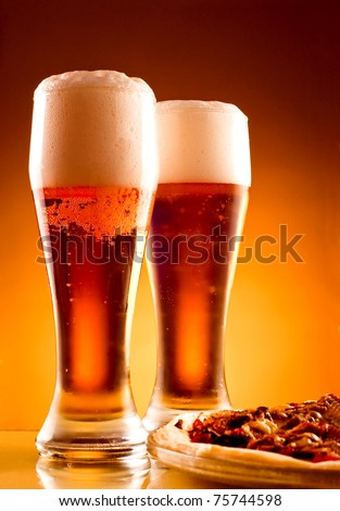 Two glass of beer and pizza over yellow background - stock photo