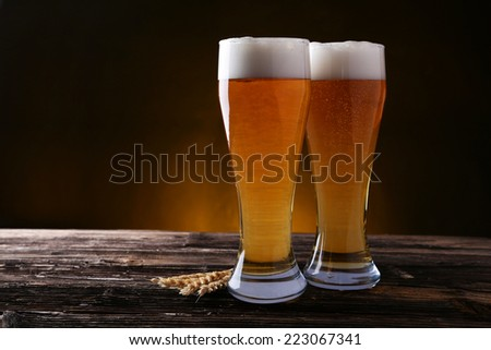 Two glass of beer on brown wooden background