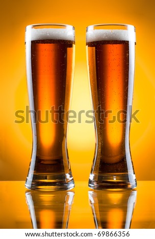 Two glass of beer over yellow background - stock photo