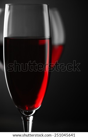 Two glass of red wine close-up on black background. Soft focus, shallow DOF. - stock photo