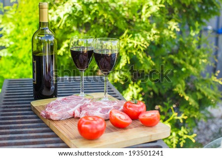 Two glass of red wine, steak and tomatoes on barbecue outdoors
