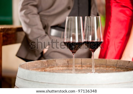 Two glass of red wine with couple standing in background