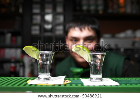 Two glass of tequila with lime at the bar - stock photo