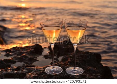 two glass of wine on the seashore with sunset. Orange sea, landscape - stock photo