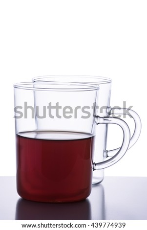Two glass tea cups, one of them empty and one with black tea isolated on white background