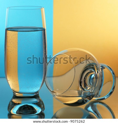 Two glass with blue yellow background. - stock photo