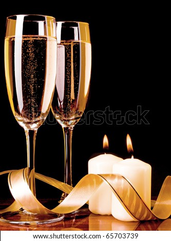 Two glass with champagne and celebratory ribbon with two burning candles - stock photo