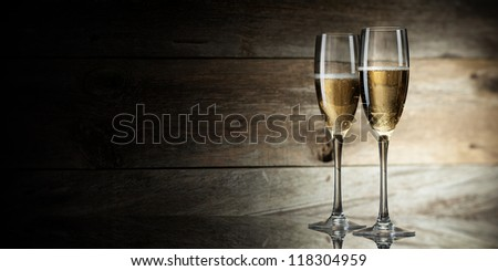 two glass with champagne on a wooden background - stock photo