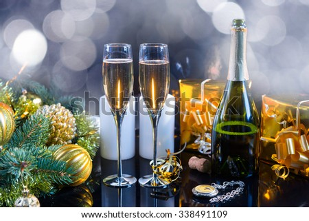 Two glasses and an open bottle of champagne surrounded by decorative pine branch, candles, golden baubles and gift boxes, next to a vintage clock, for a romantic celebration of Christmas or New Year - stock photo
