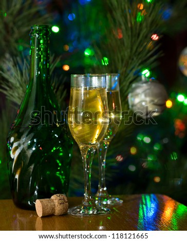 Two glasses and bottle of champagne in front of lighted christmas tree