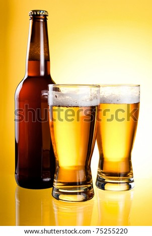 Two glasses and Bottle of fresh light beer on yellow background - stock photo