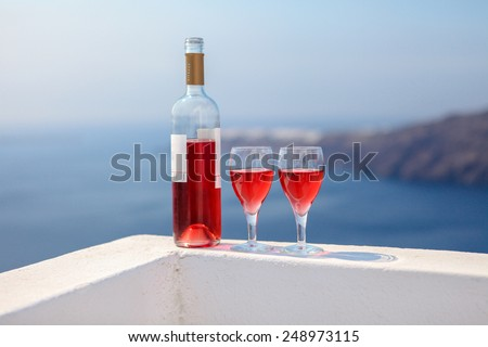 Two glasses and bottle of tasty red wine at sunset in Greece - stock photo
