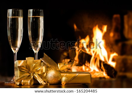 two glasses and gift boxes  in front of fireplace - stock photo
